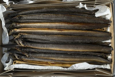 Fresh smoked eels in a cardboard box