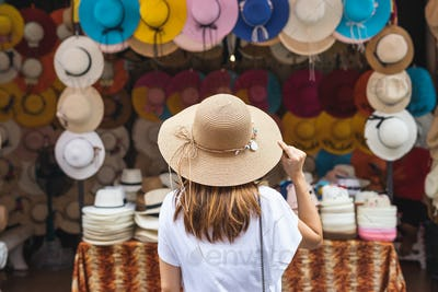 Young woman traveler looking for hat at the local market in Thailand