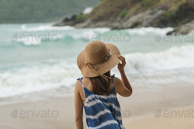 Young woman traveler standing alone at the beach on windy day