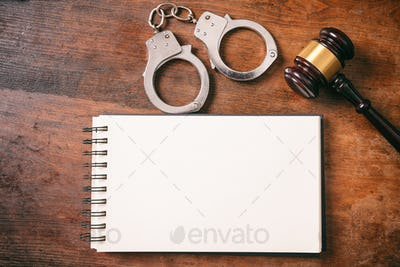 Handcuffs, gavel and notebook, copy space, on a wooden background.