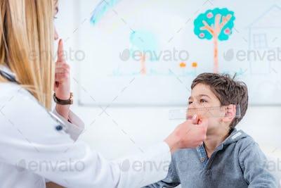 Pediatrician examining boy's eyes with ruler