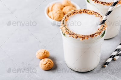 Vanilla milkshake with crispy cookies in glass mason jar on gray background