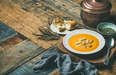 Warming pumpkin cream soup with croutons and seeds, wooden background