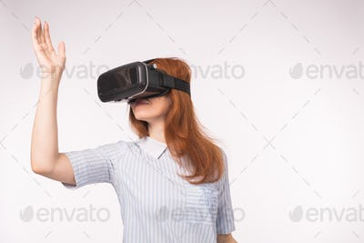Happy young red-haired woman using a virtual reality headset