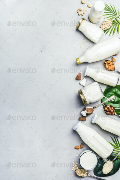 Various bottles of milk on grey concrete background