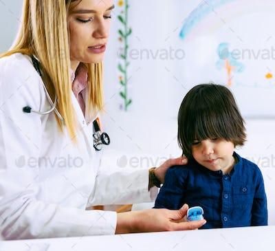 Pediatrician using finger pulse oximeter on little boy