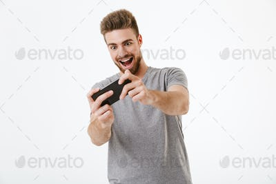 Excited young man play games by mobile phone.