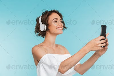 Portrait of a smiling young woman listening to music