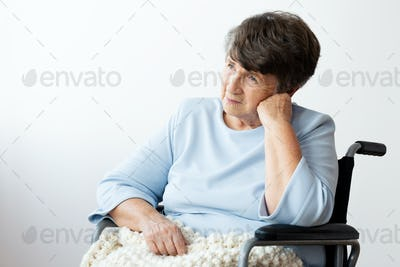 Sad disabled senior woman in a wheelchair against white backgrou