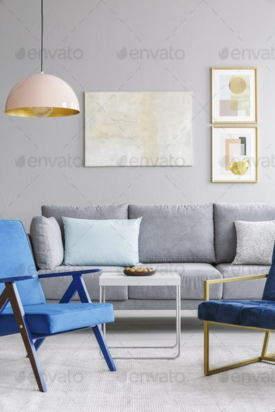 Real photo of two blue chairs standing in front of a grey couch