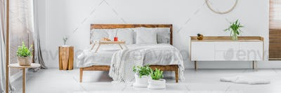 Panorama of a bright white and wooden bedroom interior with doub