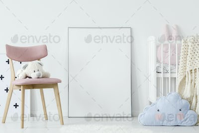 Plush toy on pink chair and blue pillow in child's room interior
