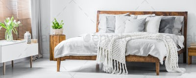Wooden framed comfortable bed with many pillows, blanket and she