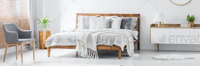 Panorama of spacious designer white bedroom interior with wooden