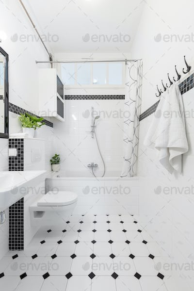 Patterned floor in white and black bathroom interior with towels