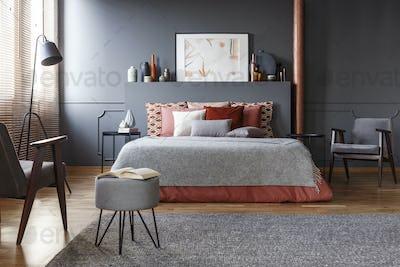 Real photo of cozy, dark bedroom interior with many decorative c