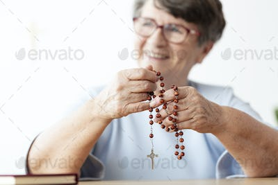 Smiling religious senior woman holding rosary with cross. Focus