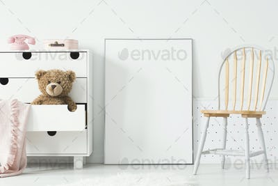 Poster with mockup between chair and cabinet with teddy bear in