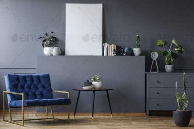 Navy blue armchair next to table in grey flat interior with mock
