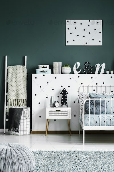 Polka dot poster on a dark green walk in a scandinavian style wh