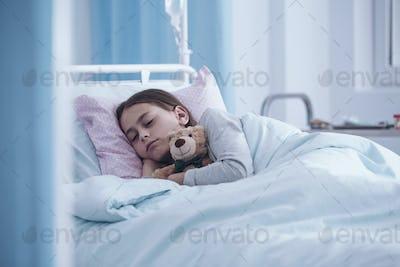 Sick girl sleeping with teddy bear in the hospital