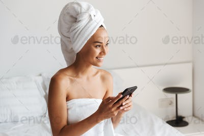 Happy young asian woman wrapped in a shower towel