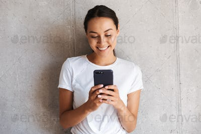 Smiling young asian woman using mobile phone