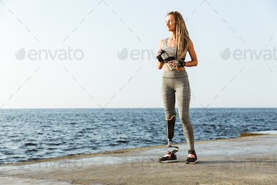 Full length of smiling disabled athlete woman