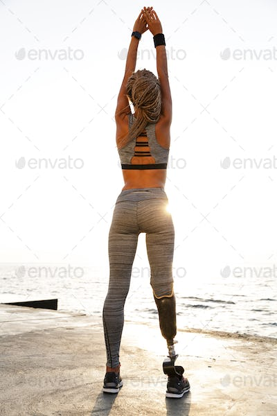 Full length back view of disabled athlete woman