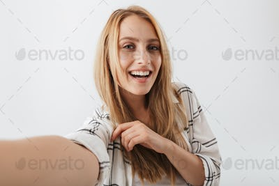 Smiling young casual girl taking selfie