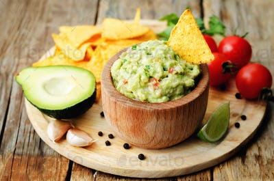Guacamole with corn chips and ingredients to prepare it