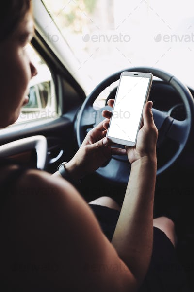 Woman looking at the screen of the smartphone in the car