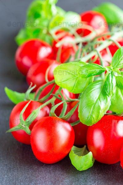 Cherry tomatoes with basil leaves on dark slate background, vert