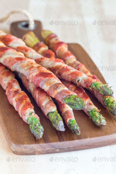 Healthy appetizer, green asparagus wrapped with bacon on wooden