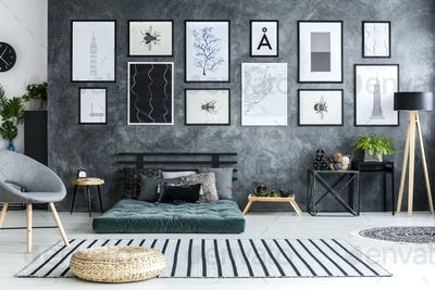 Pouf on striped rug in grey living room interior with gallery of