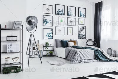 Real photo of a cozy bed standing next to a black lamp in a mono