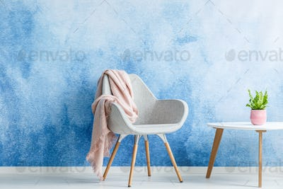 Single armchair with pastel blanket standing next to a coffee ta