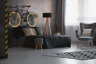 Bike above black bed in dark bedroom interior with patterned sto