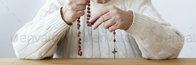 Close-up of religious senior person praying with rosary with cro