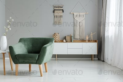 Real photo of a green armchair standing in a bright living room