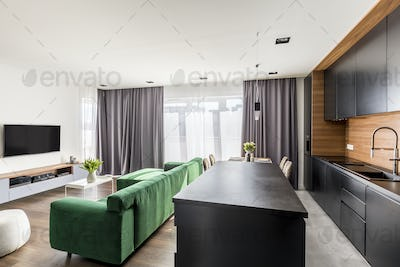 Real photo of hotel room interior with green lounge, TV set, win