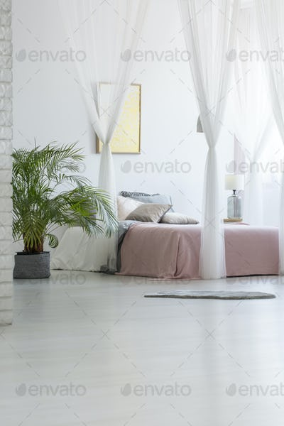 Grey rug placed on the floor in white bedroom interior with gree