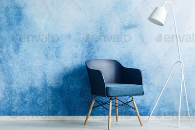 Modern dark blue chair and white metal lamp against ombre wall i