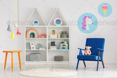 Plush toy on a blue armchair and colorful pendant lamps above an