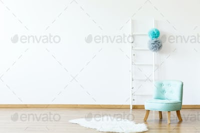 White fur next to blue chair in empty boy's room interior with c