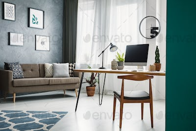 Wooden chair at desk in living room interior with work area and