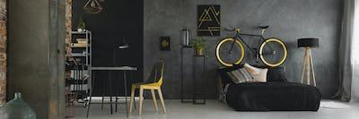 Dark studio flat interior with textured grey wall, black and yel