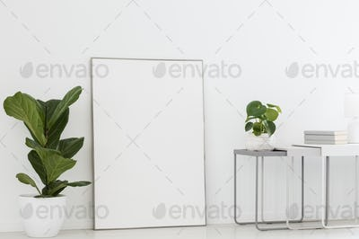 Real photo of a simple interior with a poster mockup between pla