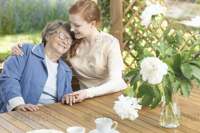 Happy grandmother enjoying time with friendly nurse on the terra