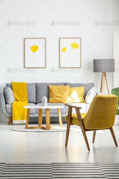 Posters with yellow flowers hanging above a gray couch in bright